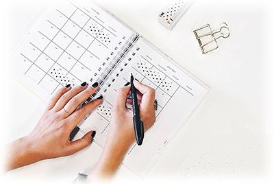 woman's hand writing on calendar